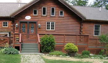 Log home with new door and deck railing